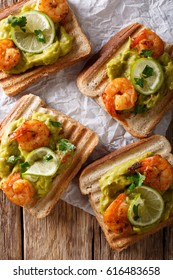 tasty Mexican sandwiches with guacamole, prawns and lime close-up on the table. Vertical view from above