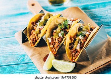 Tasty mexican tacos  with beer on a wooden table.