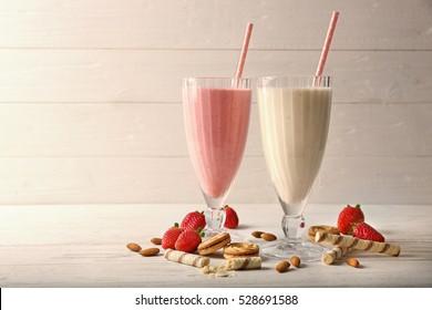 Tasty milk cocktails on wooden background