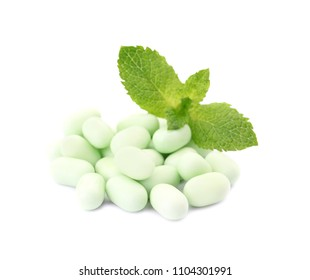 Tasty mint candies and leaves on white background