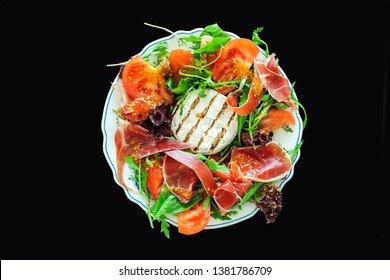 Tasty mixed salad dish with grilled camembert cheese, prosciutto ham, organic tomato and fresh green leaves. Healthy dilicious meal. Isolated on black. Flat lay