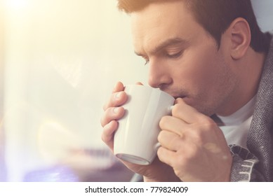 Tasty morning. Handsome dreamy thoughtful guy sipping coffee while spending the weekend morning at home and feeling cozy