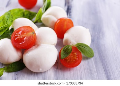 Tasty mozzarella cheese with basil and tomatoes, on wooden table