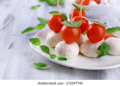 Tasty mozzarella cheese with basil and tomatoes on plate, on wooden table