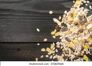Tasty muesli on black wooden background