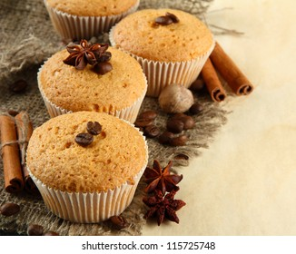 tasty muffin cakes on burlap, spices and coffee seeds, on beige background