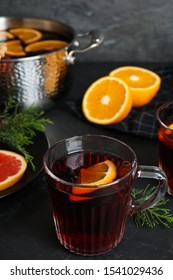 Tasty mulled wine and fresh ingredients on black table