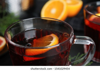 Tasty mulled wine in glass cup on table, closeup