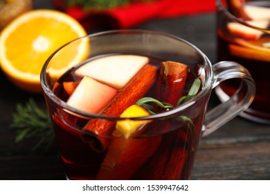Tasty mulled wine with spices in glass cup on wooden table, closeup