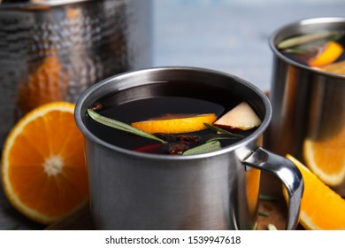 Tasty mulled wine with spices in mug on table, closeup