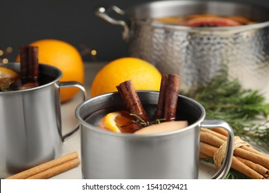 Tasty mulled wine with spices in mug on table