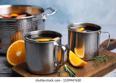 Tasty mulled wine with spices in mugs on wooden table