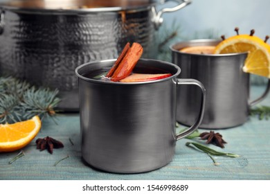 Tasty mulled wine with spices on blue wooden table