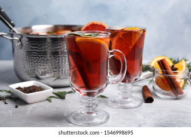 Tasty mulled wine with spices on grey marble table
