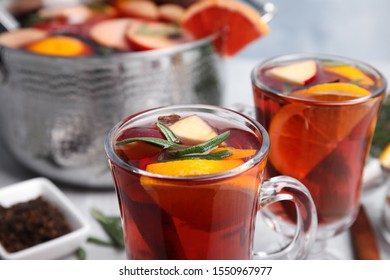 Tasty mulled wine with spices on table, closeup