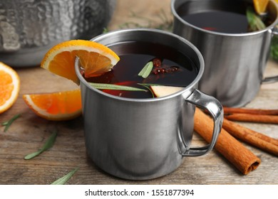 Tasty mulled wine with spices on wooden table