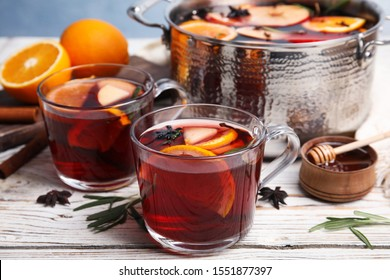 Tasty mulled wine with spices on white wooden table