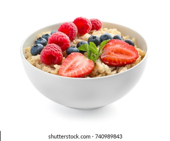 Tasty oatmeal with berries in bowl on white background