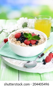 Tasty oatmeal with berries on table on bright background