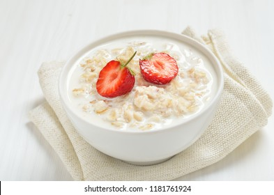 Tasty oatmeal with strawberry slices in bowl, close up