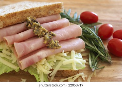 Tasty open sandwich with green lettuce, grated cheese, smoked ham and wholegrain mustard on wholewheat bread with rosemary and tomatoes on chopping board