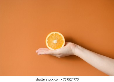 Tasty orange in a hand. holding a orange isolated on a colored background