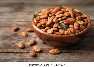 Tasty organic almond nuts in bowl on table