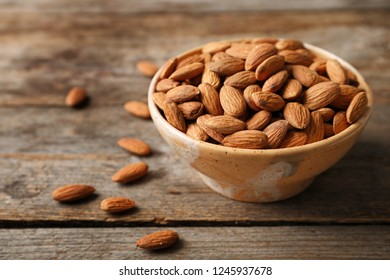 Tasty organic almond nuts in bowl on table. Space for text