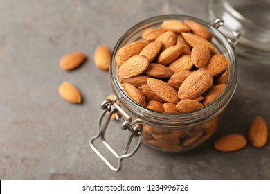 Tasty organic almond nuts in glass jar on table. Space for text
