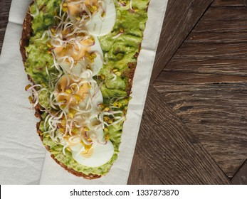 Tasty organic bread with Avocado cream and eggs on a rustic wooden table