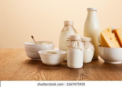 tasty organic dairy products on rustic wooden table isolated on beige