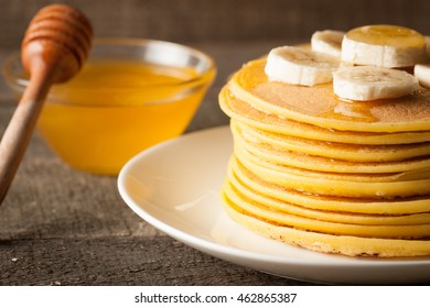 Tasty pancakes with blackberries, banana, raspberries, eggs, honey and maple syrup on wooden background. Morning breakfast concept.