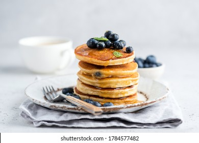 Tasty pancakes with blueberries and honey on a plate. Grey background
