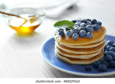 Tasty pancakes with blueberries and mint on table