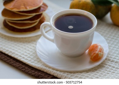 Tasty pancakes with a cup of coffee and tangerine on a white table