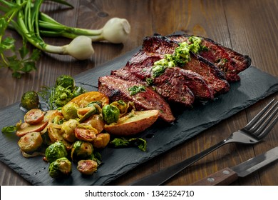 Tasty Pan-Seared Hanger Steak with brussels sprouts, potatoes and onion meal ona  table. Healthy home-made food.