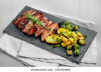 Tasty Pan-Seared Hanger Steak with brussels sprouts, potatoes and onion meal on a white wooden table. Healthy home-made food.