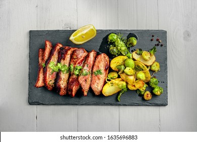 Tasty Pan-Seared Hanger Steak with brussels sprouts, potatoes and onion meal on a white wooden table. Healthy home-made food. Top view above.