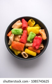 Tasty Papad Pipe Fryum is a multicolour potato based snack pellets in Tubular Circular shape, served in a bowl