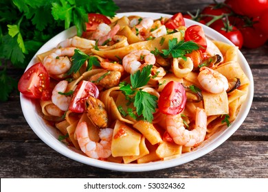 Tasty Pappardelle pasta with shrimp, Squid, mussel, tomatoes and herbs.