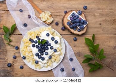 Tasty pasta with fresh organic blueberries and vanilla cream. Sweet dinner on retro wooden table.