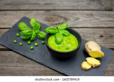 tasty pea soup with basil and ginger on black slate.