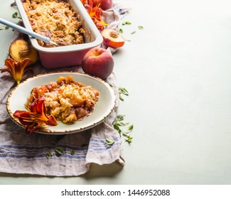 Tasty peach crumble dessert in plate on light background with baking pan and fresh peaches . Copy space
