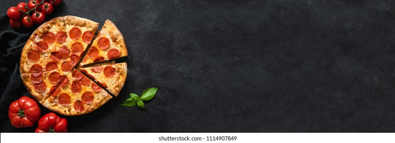 Tasty pepperoni pizza and cooking ingredients tomatoes basil on black concrete background. Top view of hot pepperoni pizza. Banner