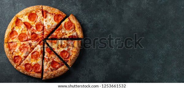 Tasty pepperoni pizza and cooking ingredients tomatoes basil on black concrete background. Top view of hot pepperoni pizza. With copy space for text. Flat lay. Banner