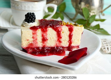 Tasty piece of cheesecake with berry sauce on plate on table close up