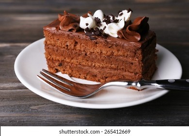 Tasty piece of chocolate cake on wooden table background