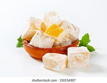 Tasty pieces of orange turkish delight in a ceramic bowl