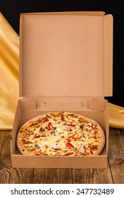Tasty pizza in box on wooden table. Located on a black background.