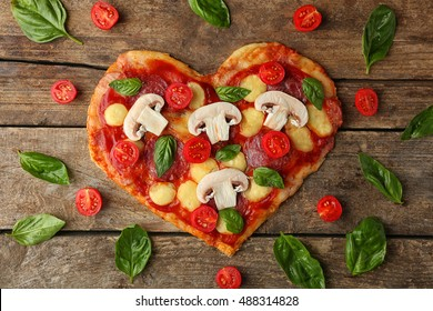 Tasty pizza in heart shape with basil leaves and tomatoes on table